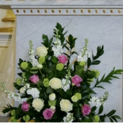 Church pedestal of Roses, Ranunculus, Stock and Viburnum and hard Ruscus