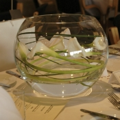 Fish bowl table centre of white Calla Lilies and Bear grass